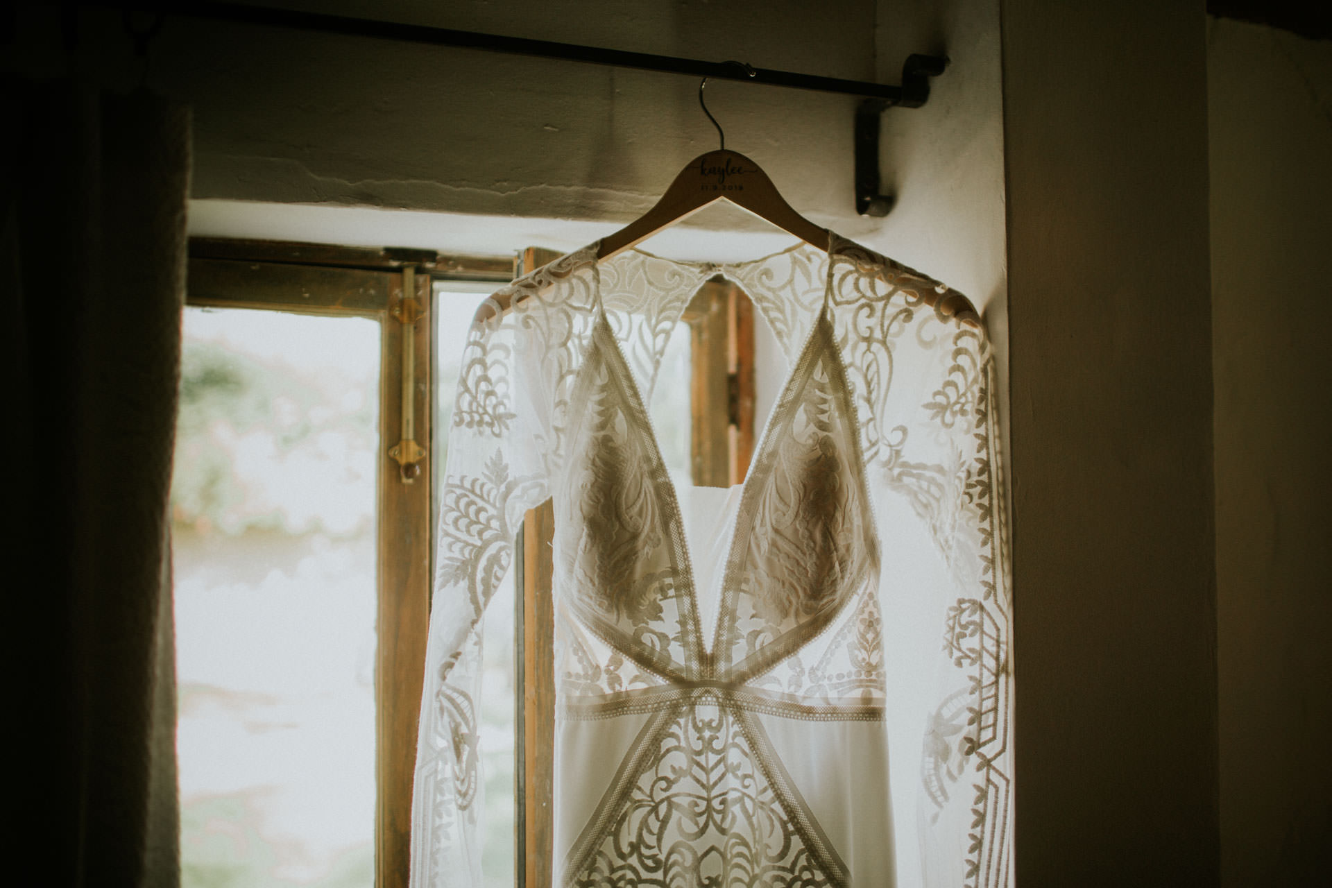 bohemian style lace wedding dress hanging from a window